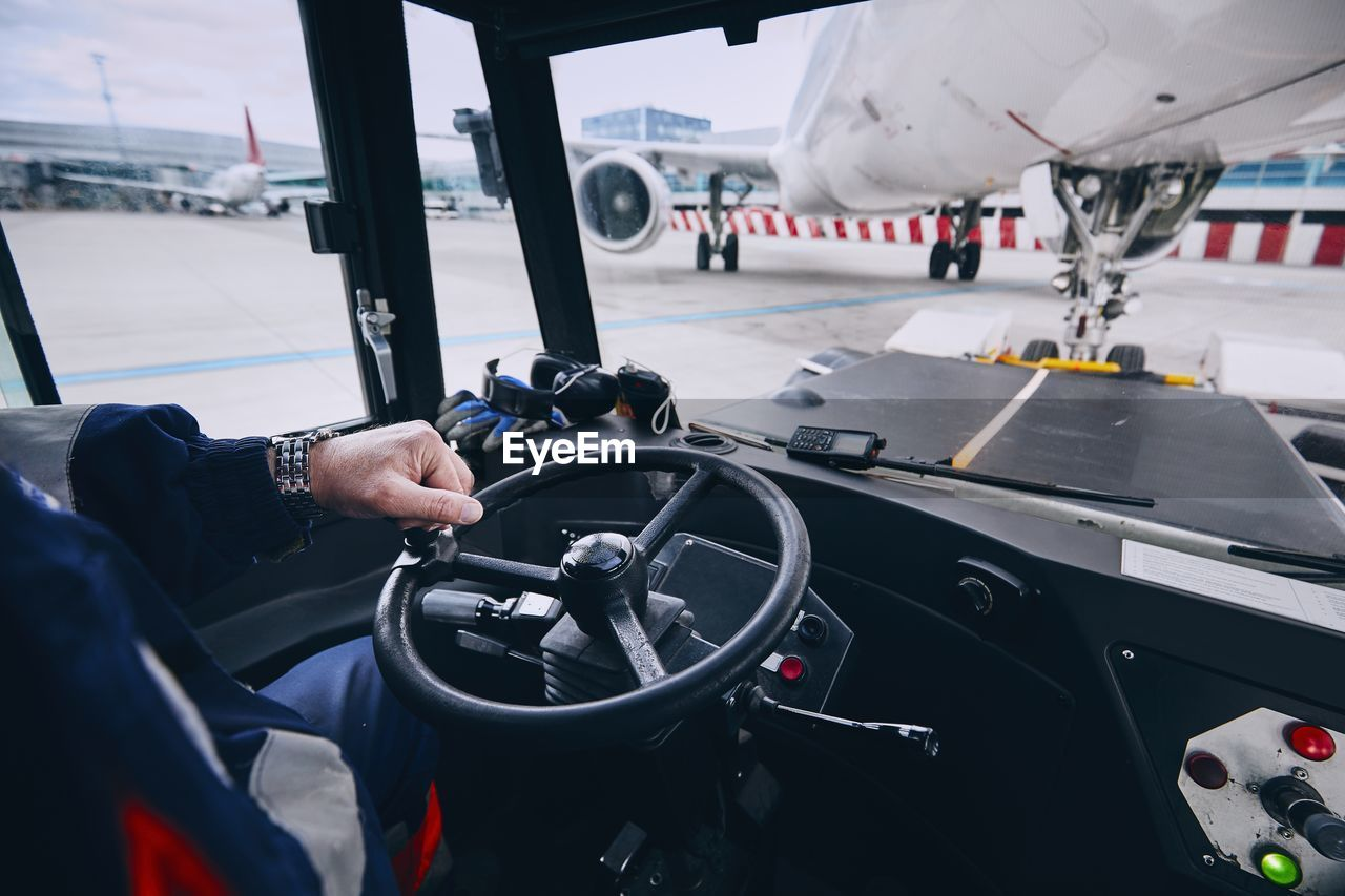 transportation, mode of transportation, real people, one person, human hand, control, hand, travel, vehicle interior, air vehicle, airplane, day, men, human body part, holding, car, windshield, unrecognizable person, control panel, land vehicle, outdoors, finger, aerospace industry, responsibility