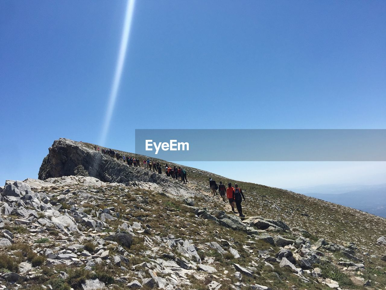 sky, nature, rock, lifestyles, leisure activity, beauty in nature, copy space, real people, day, rock - object, clear sky, tranquility, solid, scenics - nature, people, sunlight, tranquil scene, blue, mountain, men, outdoors