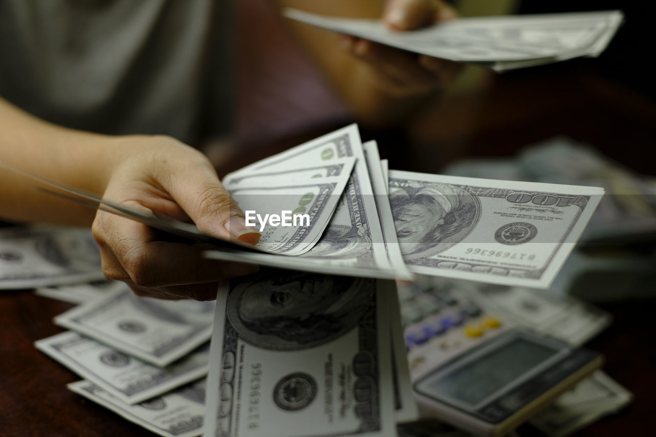 human hand, currency, paper currency, finance, hand, one person, business, holding, human body part, real people, indoors, wealth, savings, close-up, unrecognizable person, selective focus, midsection, paying, finger