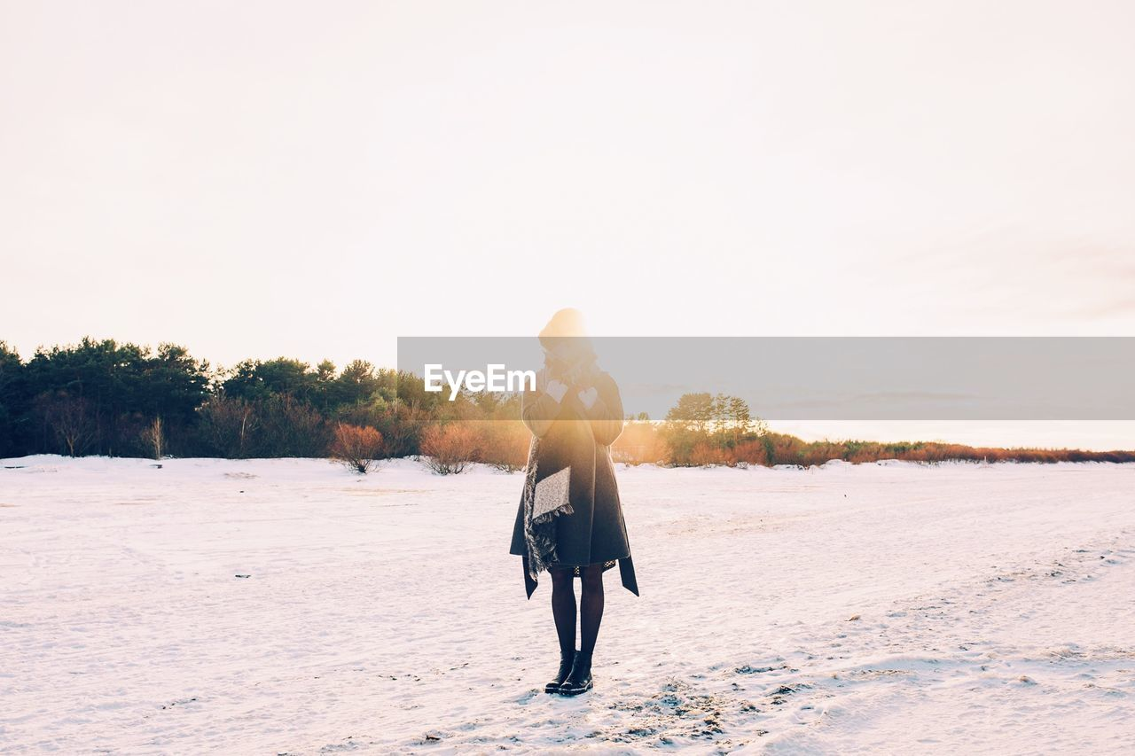 Full Length Of Woman Standing On Snow Covered Field Against Clear Sky