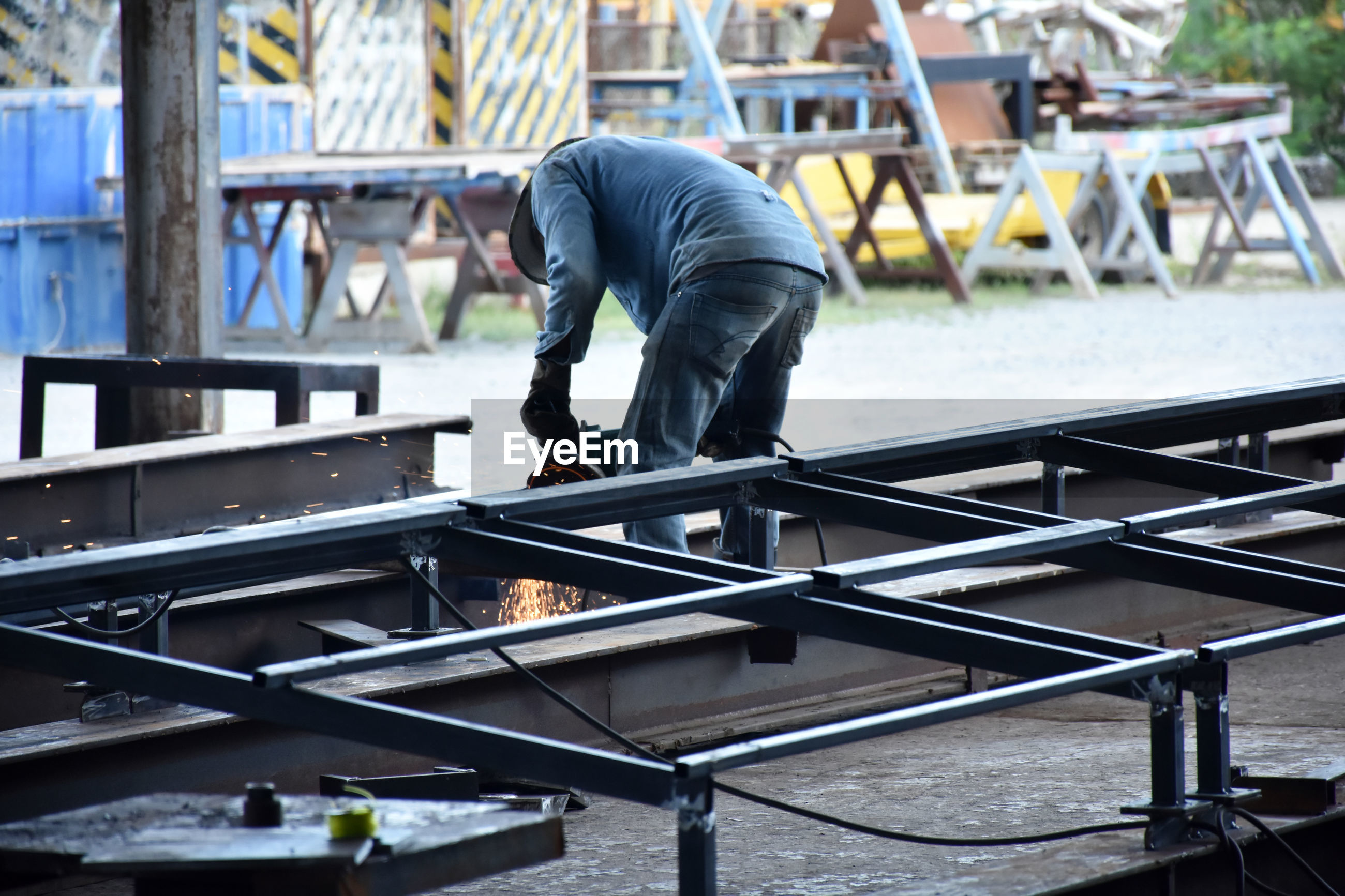 FULL LENGTH OF MAN WORKING ON METAL RAILING
