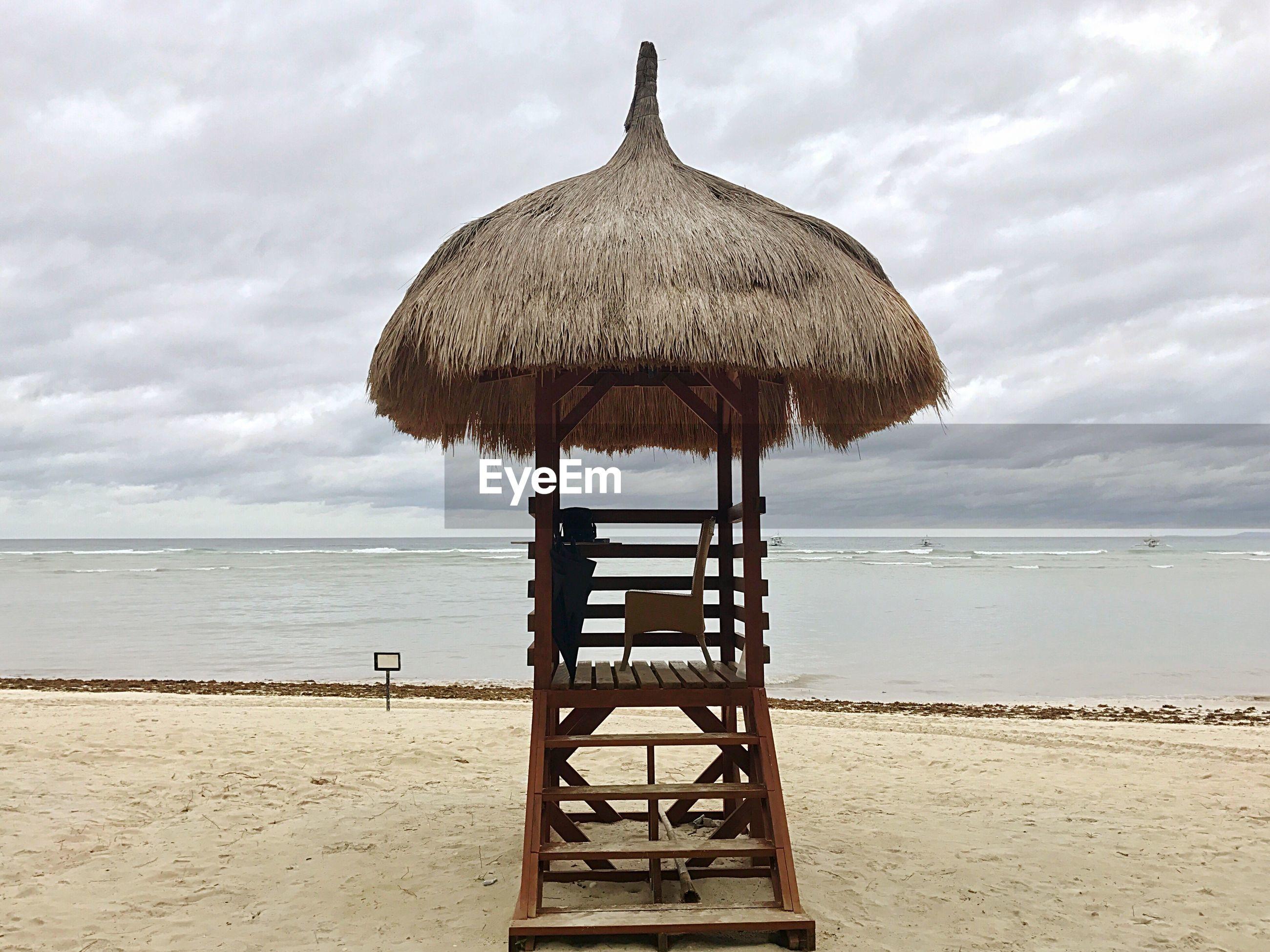 Lifeguard hut at beach against cloudy sky
