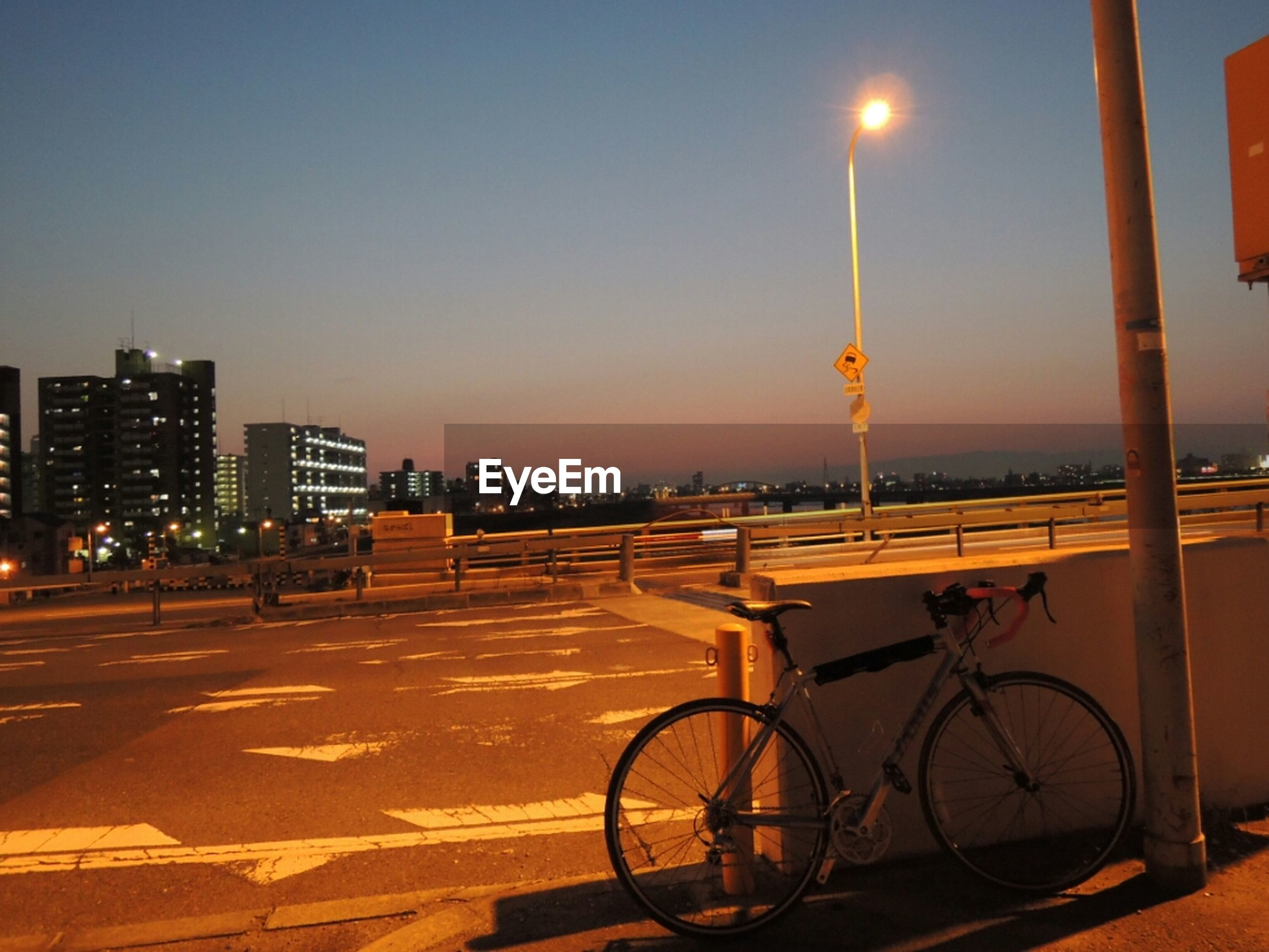 bicycle, street light, transportation, illuminated, architecture, built structure, building exterior, clear sky, street, land vehicle, mode of transport, sunset, city, lighting equipment, copy space, stationary, parking, parked, night, sky