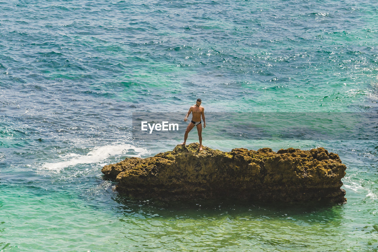 water, sea, real people, leisure activity, shirtless, rock, rock - object, lifestyles, solid, waterfront, one person, nature, land, day, standing, beauty in nature, motion, men, outdoors
