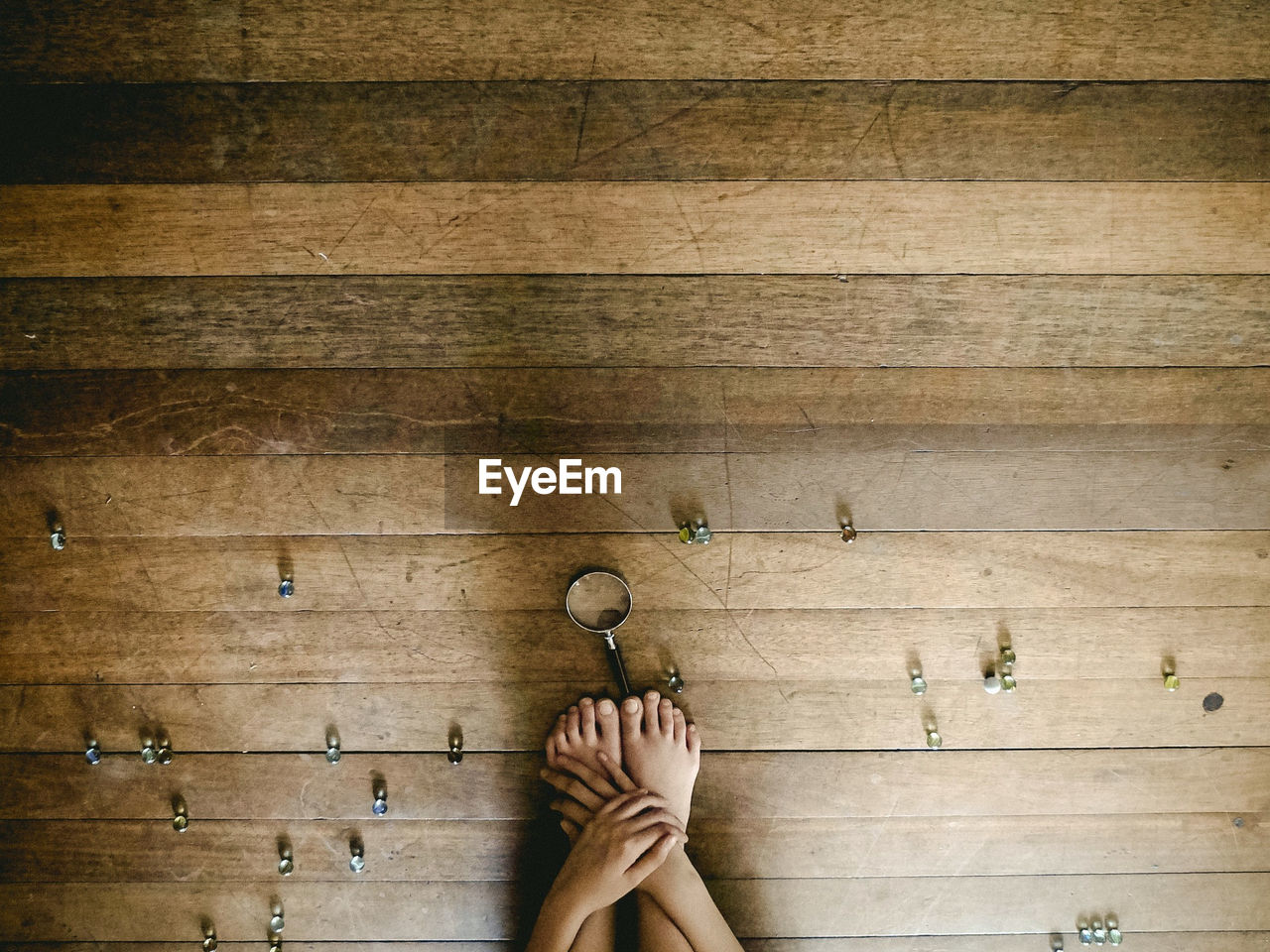Cropped image of person crouching with marbles and magnifying glass on hardwood floor