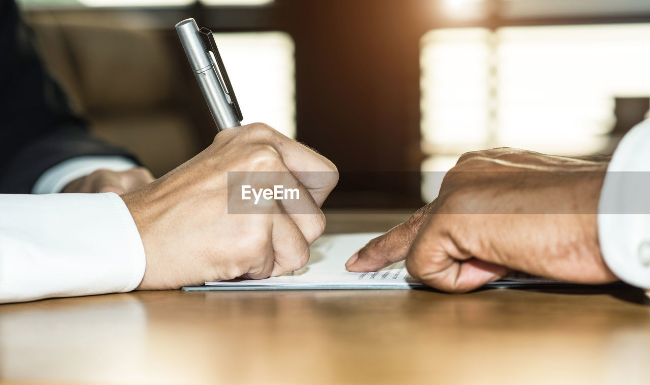Midsection of man signing on documents over table