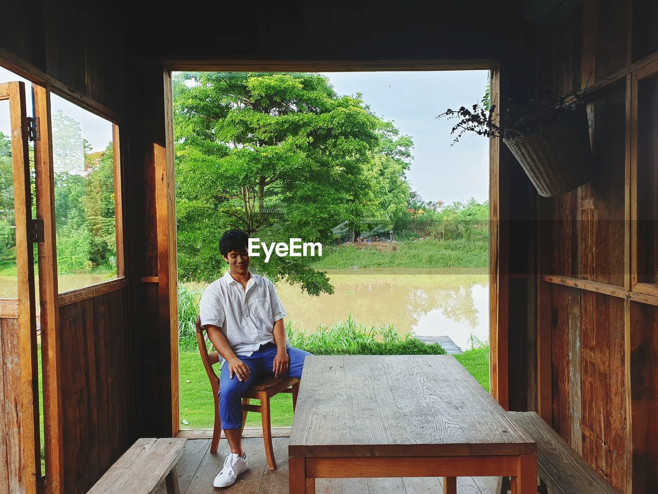 Smiling man sitting on chair in cottage by lake