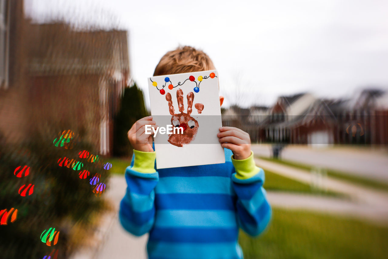 Boy covering face with handprint on paper against sky