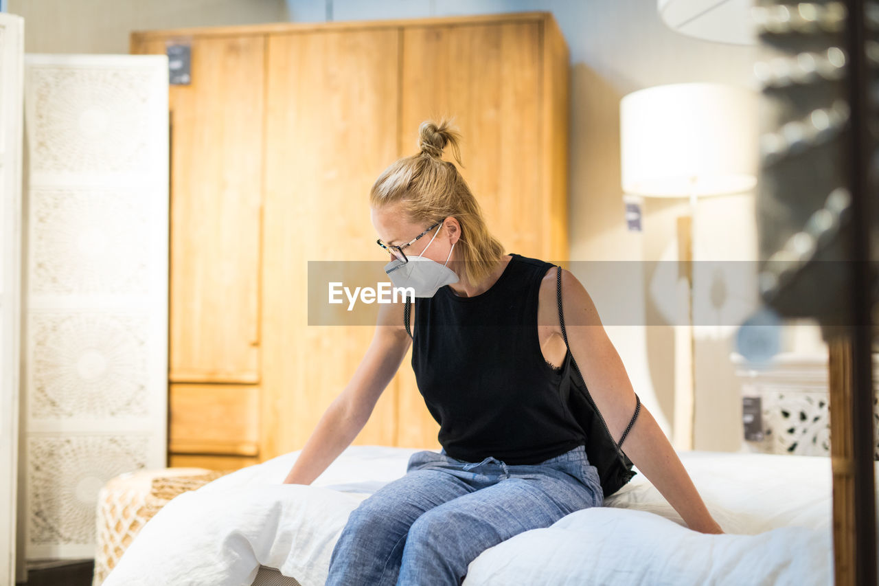 Woman wearing flu mask sitting on bed at store