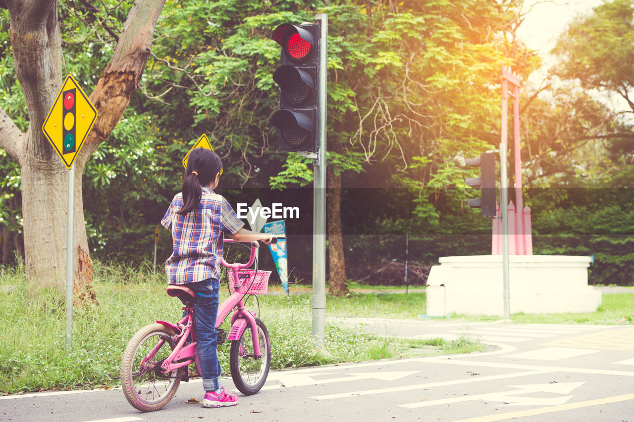 transportation, real people, plant, tree, child, road, lifestyles, rear view, one person, casual clothing, land vehicle, nature, full length, childhood, ride, leisure activity, mode of transportation, riding, day, outdoors