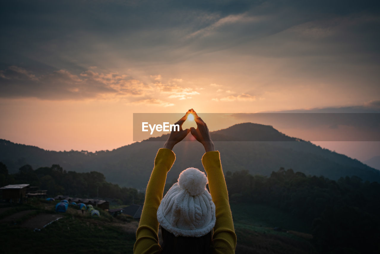 Rear View Of Woman Gesturing Against Sky During Sunset