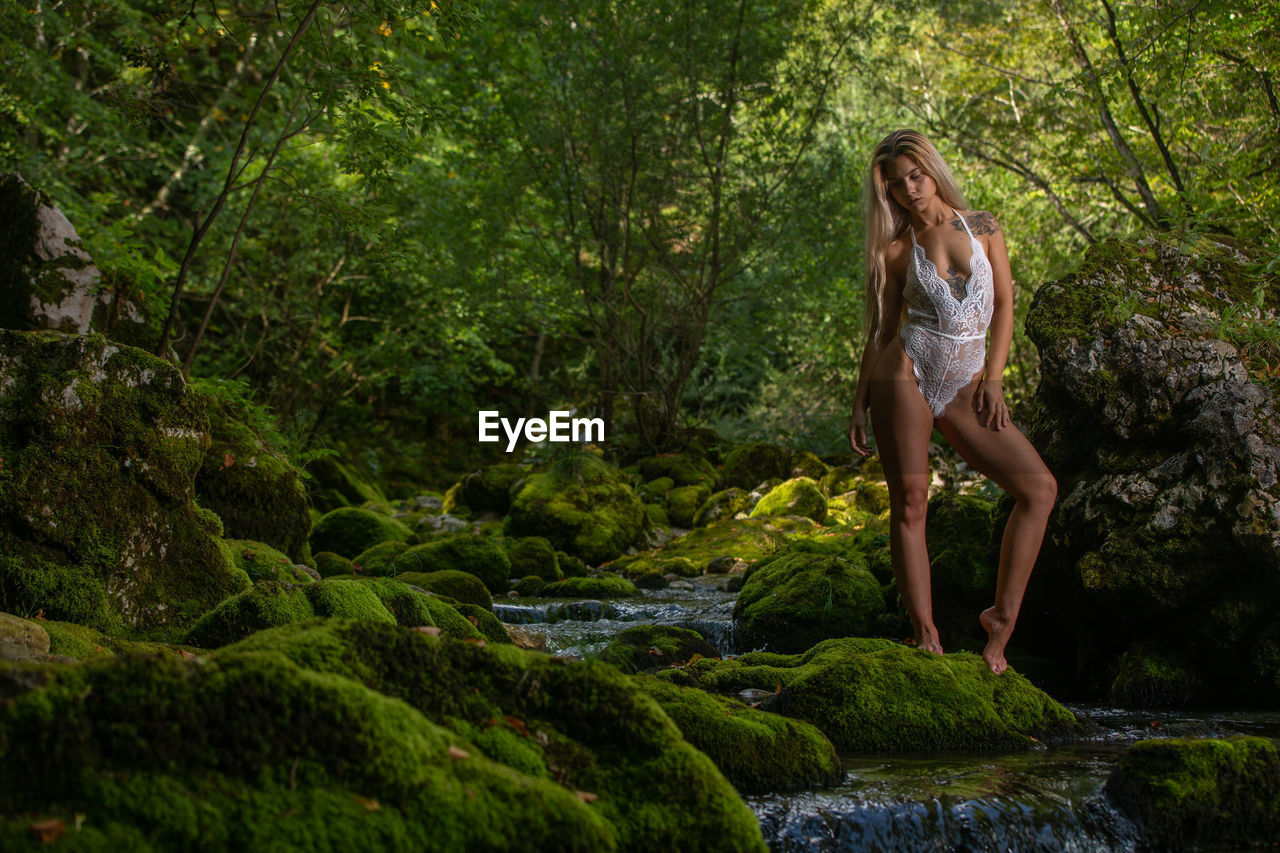 Full Length Of Young Woman In Bikini Standing On Rock Against Trees At Forest