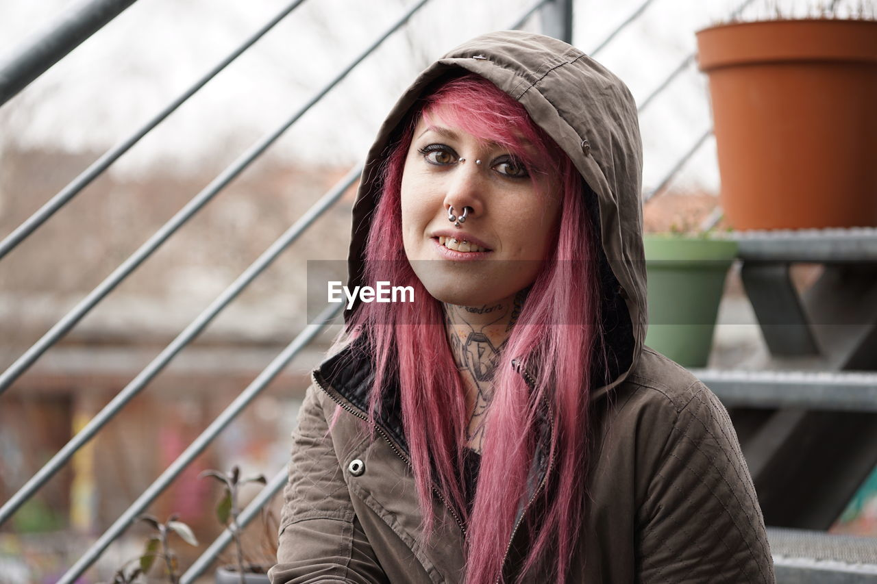 Portrait of smiling woman with pink hair and hooded shirt