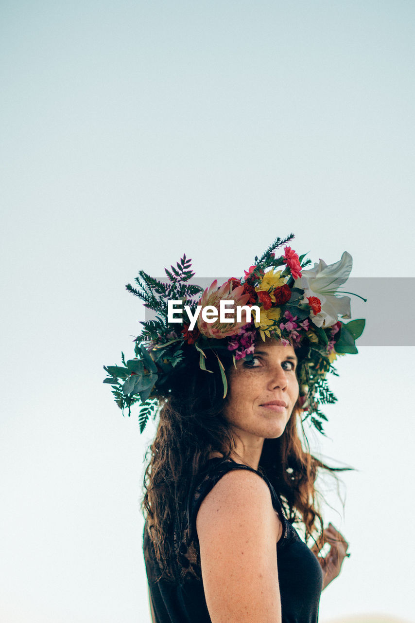 Woman wearing multi colored flowers against clear sky