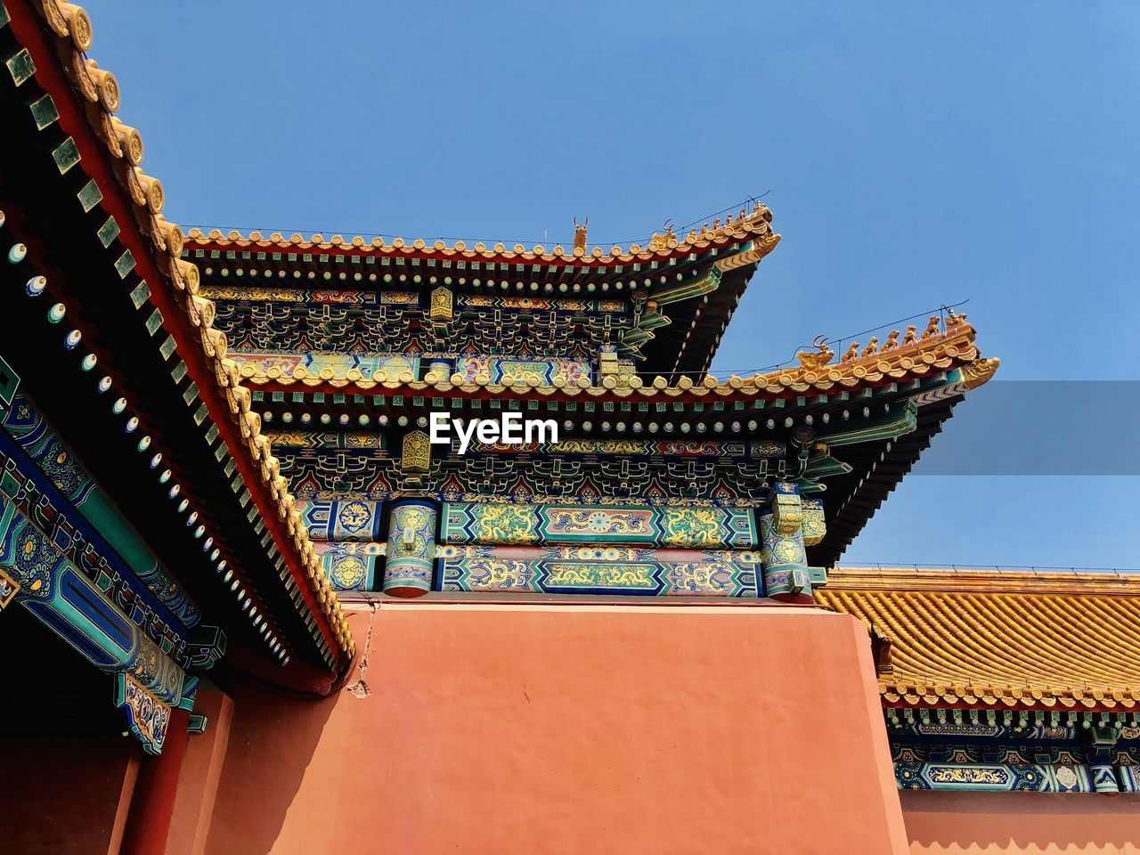 LOW ANGLE VIEW OF TEMPLE ROOF AGAINST BUILDING
