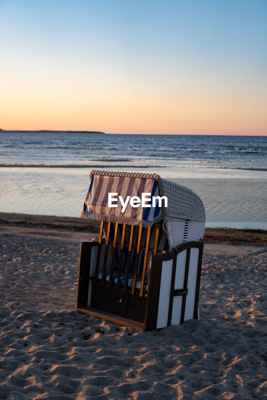 sea, water, beach, horizon over water, beauty in nature, horizon, scenics - nature, land, sky, tranquility, sunset, tranquil scene, nature, sand, hooded beach chair, absence, idyllic, no people, chair, outdoors