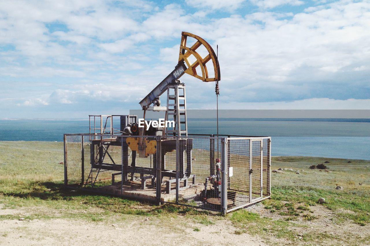Oil Pump By Sea Against Sky