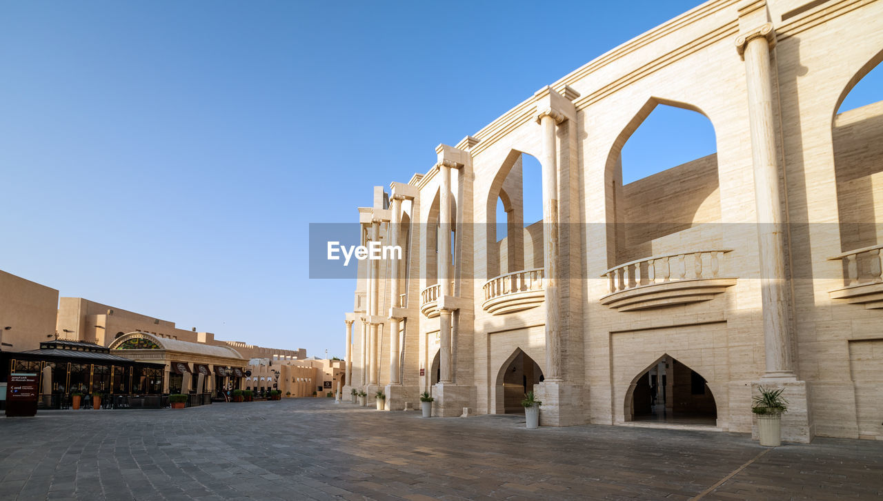 architecture, built structure, building exterior, sky, clear sky, history, arch, the past, building, travel destinations, blue, day, nature, sunlight, travel, architectural column, tourism, place of worship, religion, belief, outdoors, no people, ancient civilization, courtyard