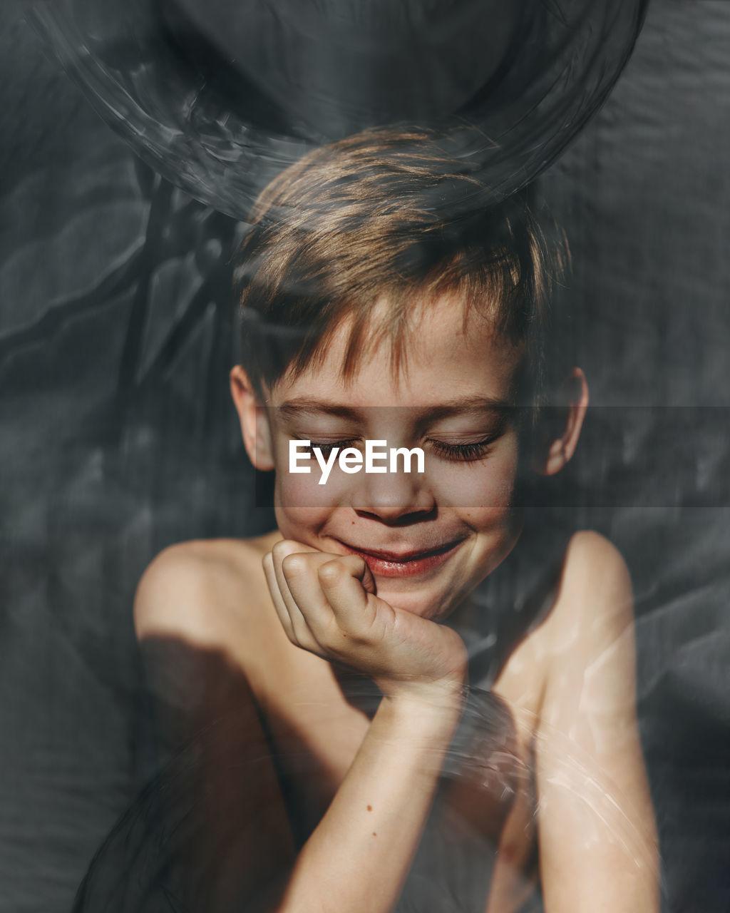 Close-Up Of Shirtless Boy Smiling Seen Through Glass