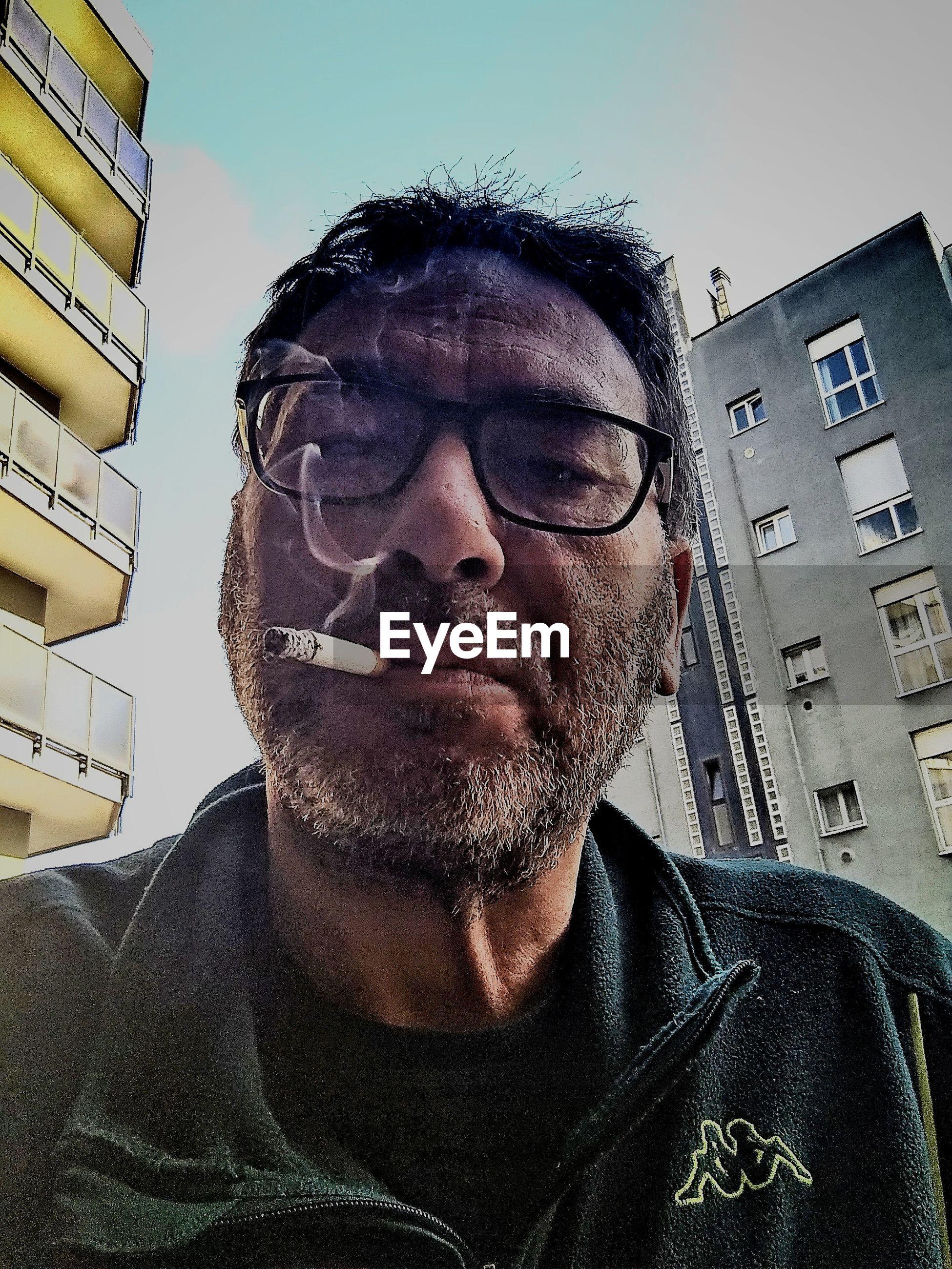 PORTRAIT OF MID ADULT MAN WEARING EYEGLASSES