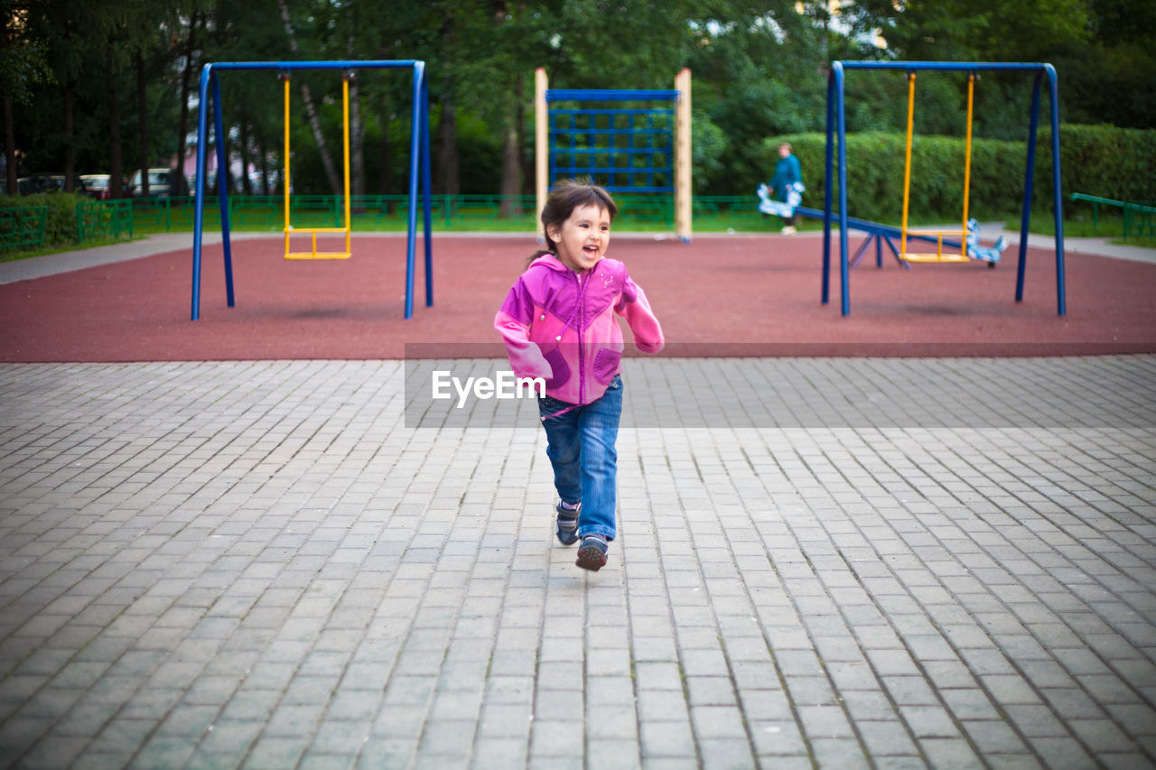 Cute girl running on footpath at playground