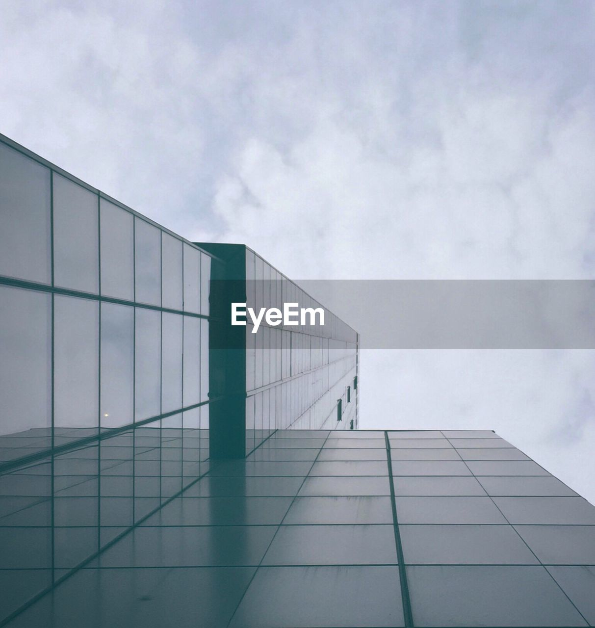 Directly Below Shot Of Modern Glass Building Against Cloudy Sky