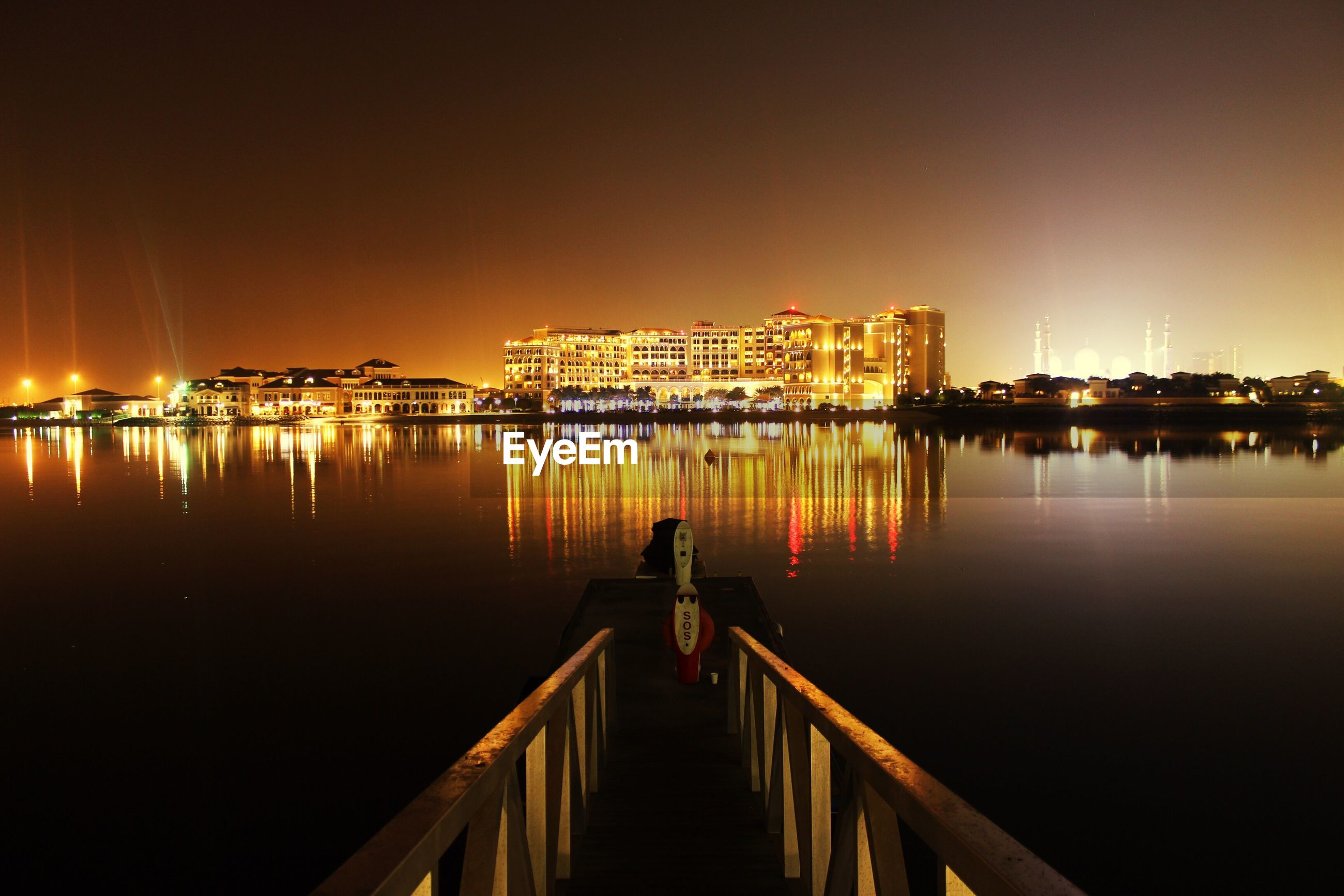 Pier on lake by illuminated buildings against sky at dusk