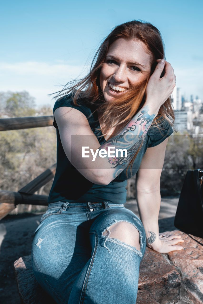 real people, one person, casual clothing, smiling, leisure activity, lifestyles, portrait, looking at camera, young adult, sitting, women, hair, young women, long hair, three quarter length, beautiful woman, hairstyle, day, outdoors, jeans