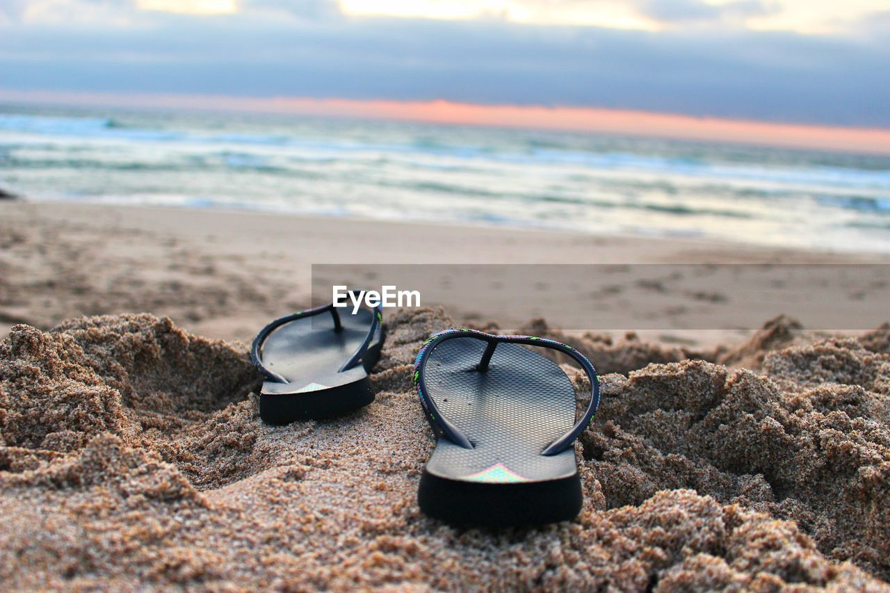 CLOSE-UP OF SUNGLASSES SHOES ON BEACH