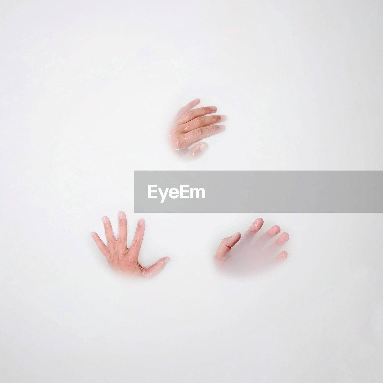 Cropped Hands Of People In Milkbath