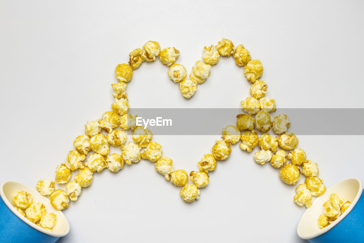 white background, studio shot, indoors, still life, jewelry, no people, gold colored, close-up, art and craft, wealth, creativity, love, yellow, luxury, large group of objects, high angle view, necklace, pattern, heart shape, gold, personal accessory, precious gem, expense