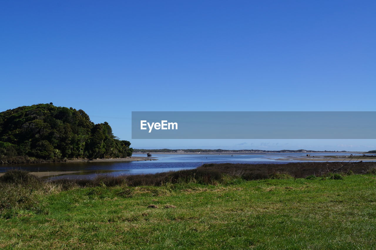 sky, water, tranquility, beauty in nature, land, copy space, tranquil scene, clear sky, sea, scenics - nature, nature, grass, beach, plant, no people, blue, day, non-urban scene, idyllic, outdoors