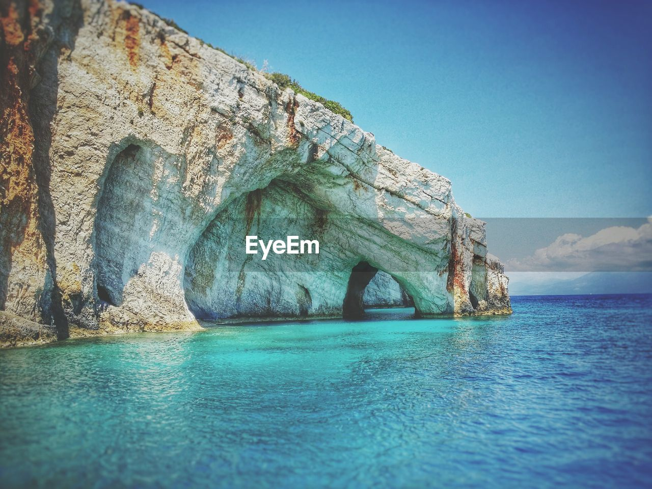 Caves by blue sea against sky at zakynthos