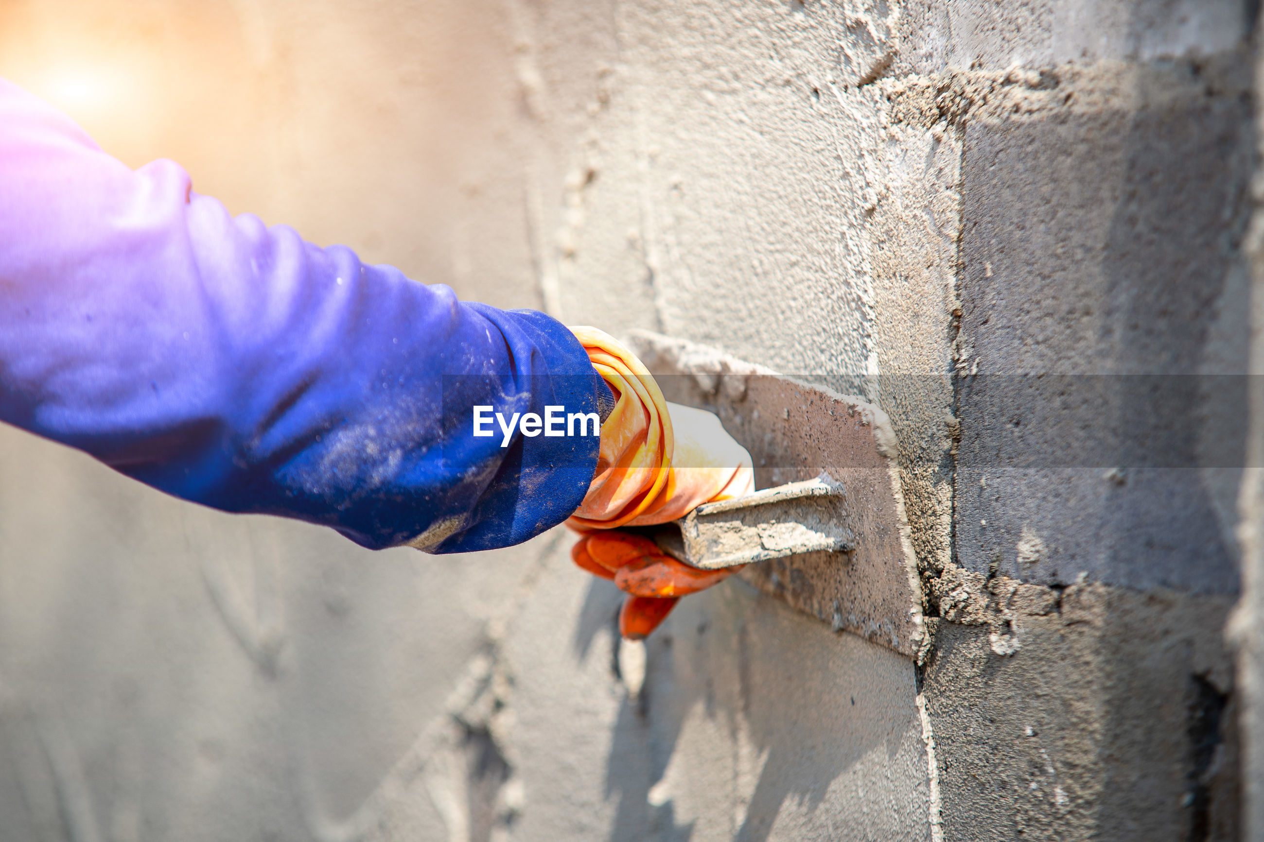 MIDSECTION OF MAN WORKING ON WALL