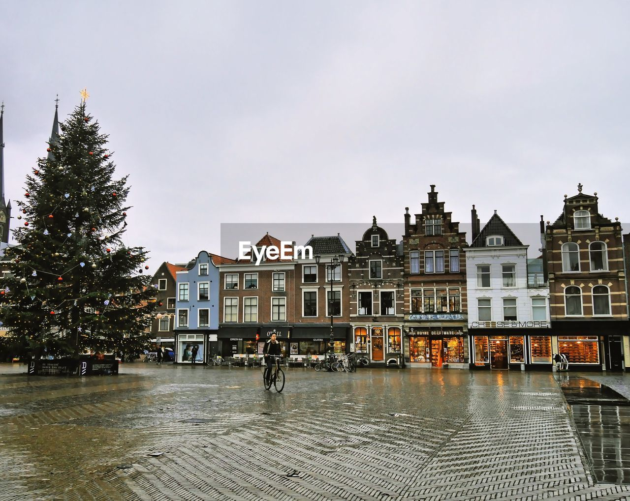 Buildings By Wet Street Against Sky In City During Christmas