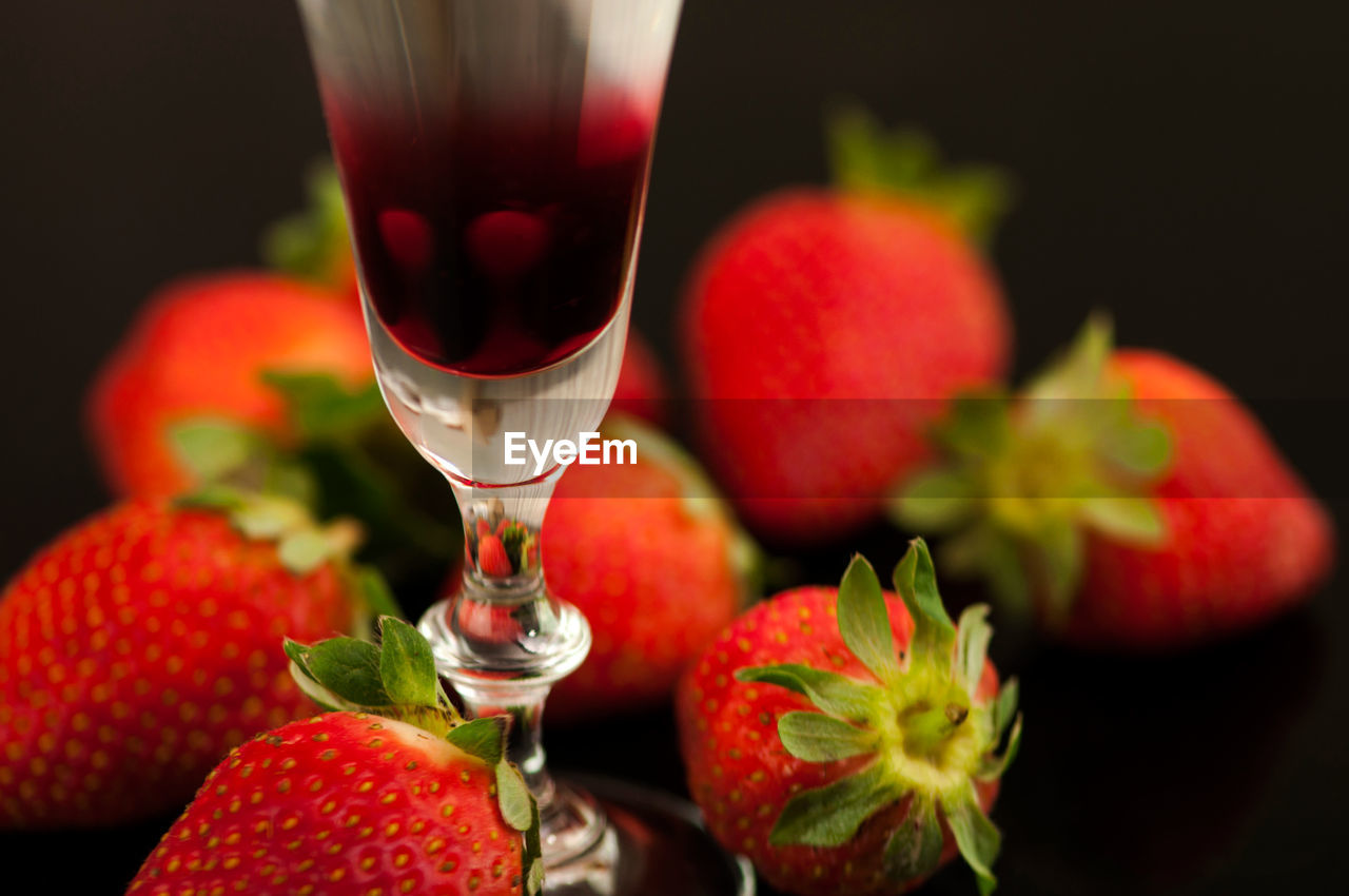 red, food and drink, fruit, glass, freshness, strawberry, berry fruit, healthy eating, food, close-up, refreshment, drink, alcohol, no people, drinking glass, household equipment, indoors, still life, wellbeing, glass - material, black background
