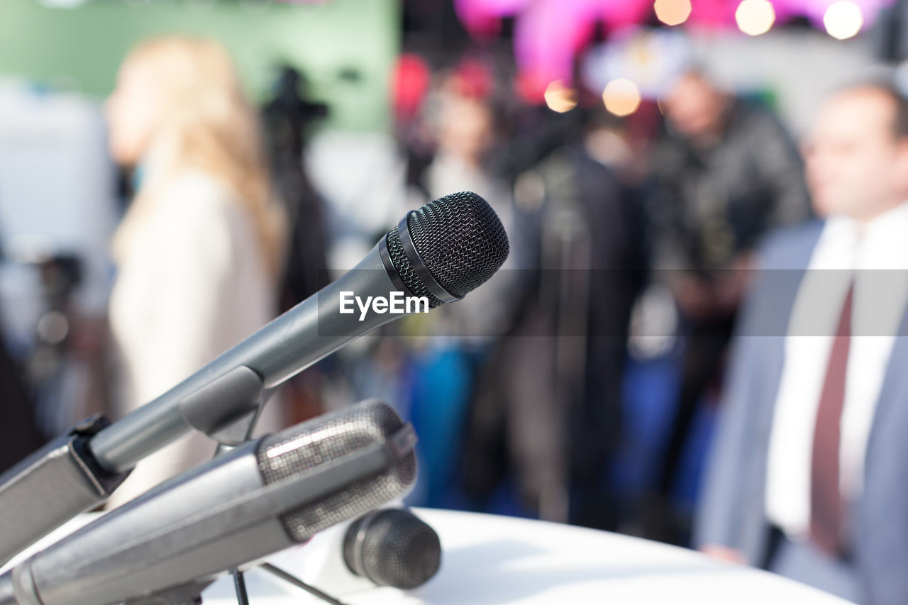 Close-Up Of Microphone With People In Background