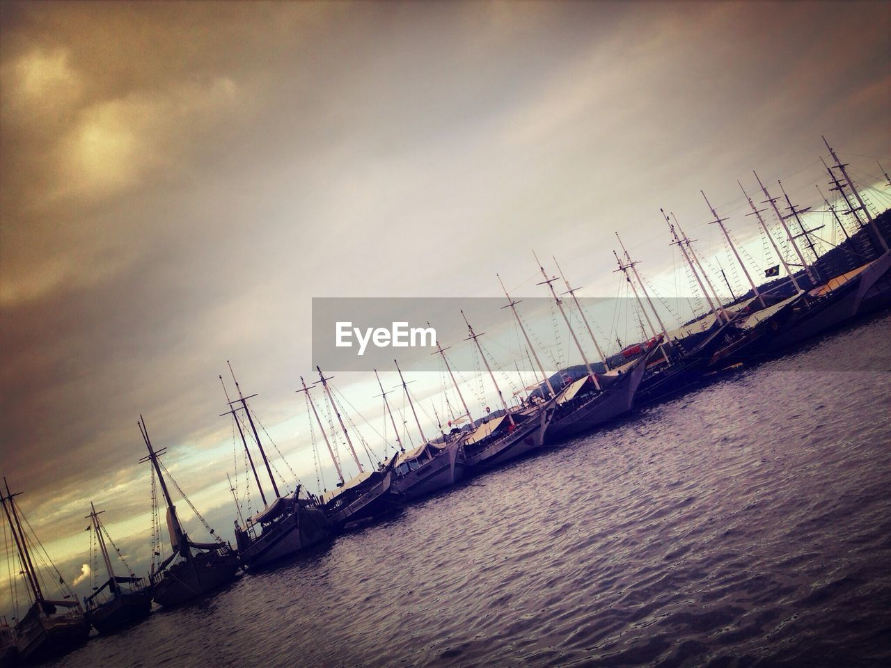 Tilt Image Of Boats Moored On River Against Cloudy Sky