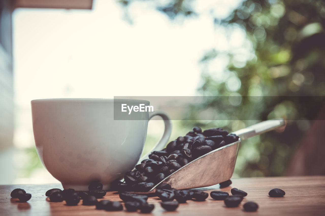 Close-up of roasted coffee beans with cup on table