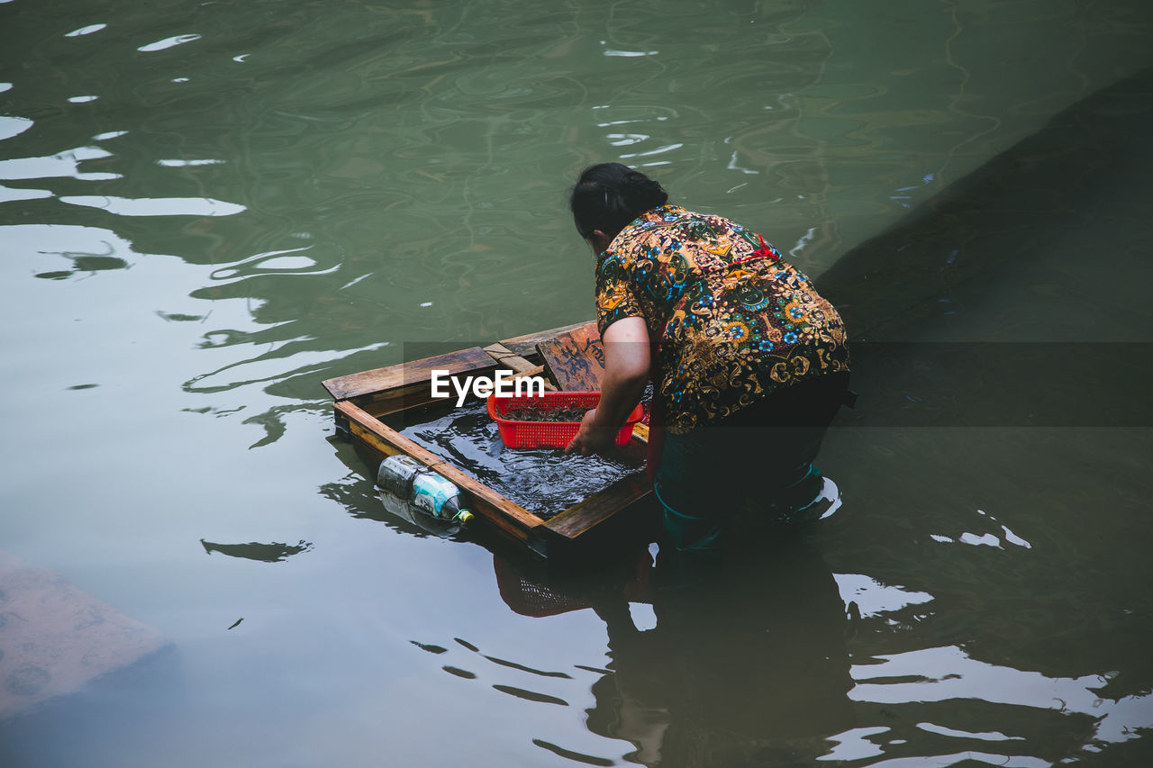 High angle view of woman fishing in lake