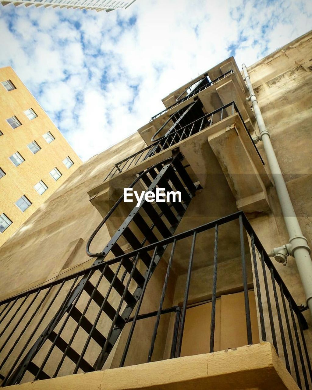 architecture, low angle view, built structure, building exterior, window, sky, day, cloud - sky, no people, outdoors, fire escape