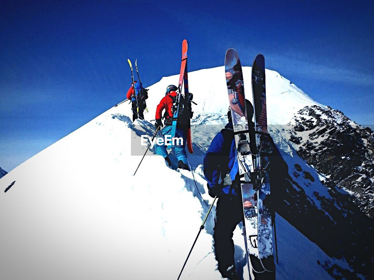 Rear view of people climbing snow covered mountain against sky