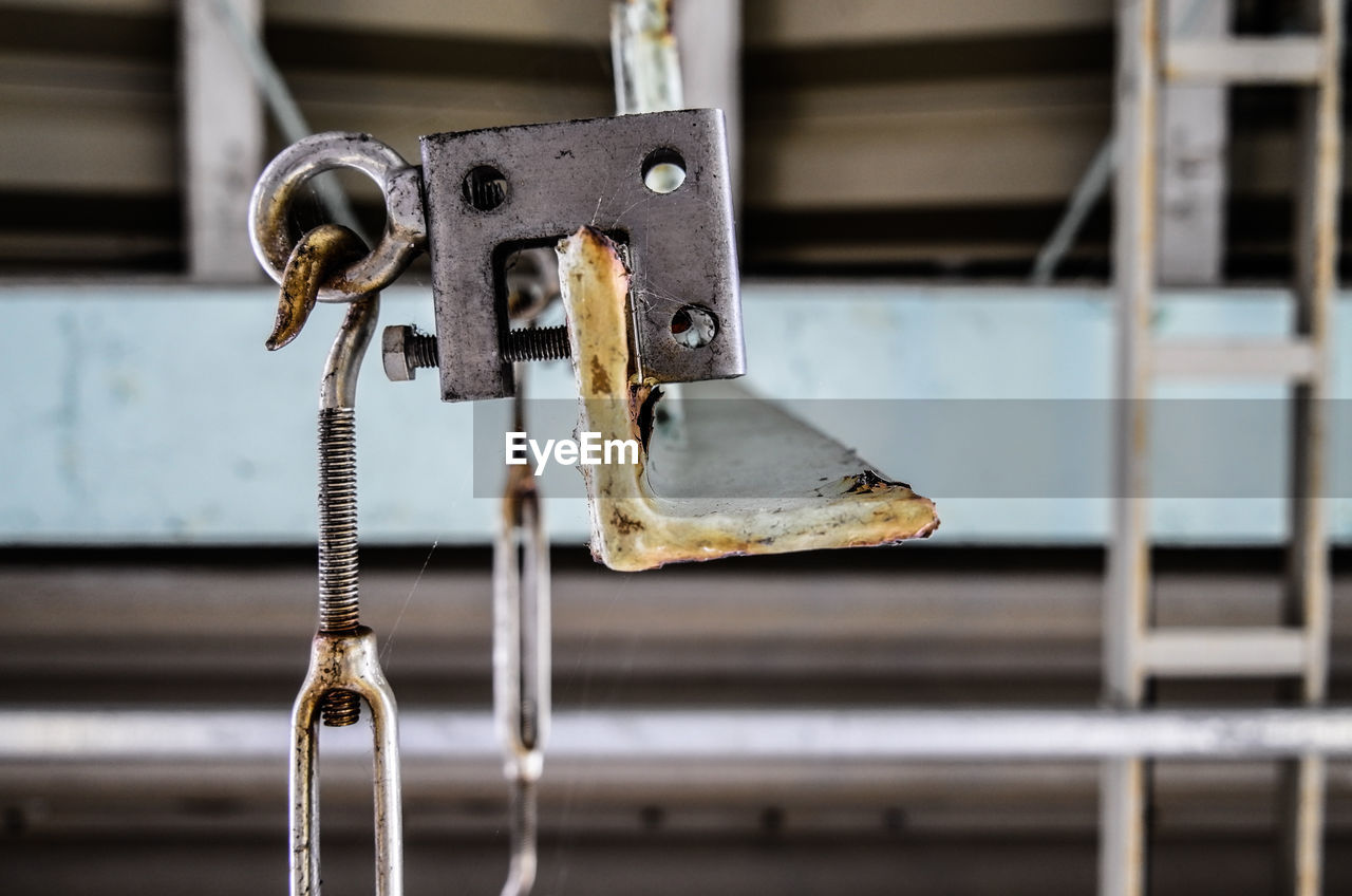 metal, focus on foreground, no people, close-up, indoors, rusty, machinery, industry, old, hanging, weathered, day, abandoned, selective focus, equipment, security, connection, factory, damaged, silver colored