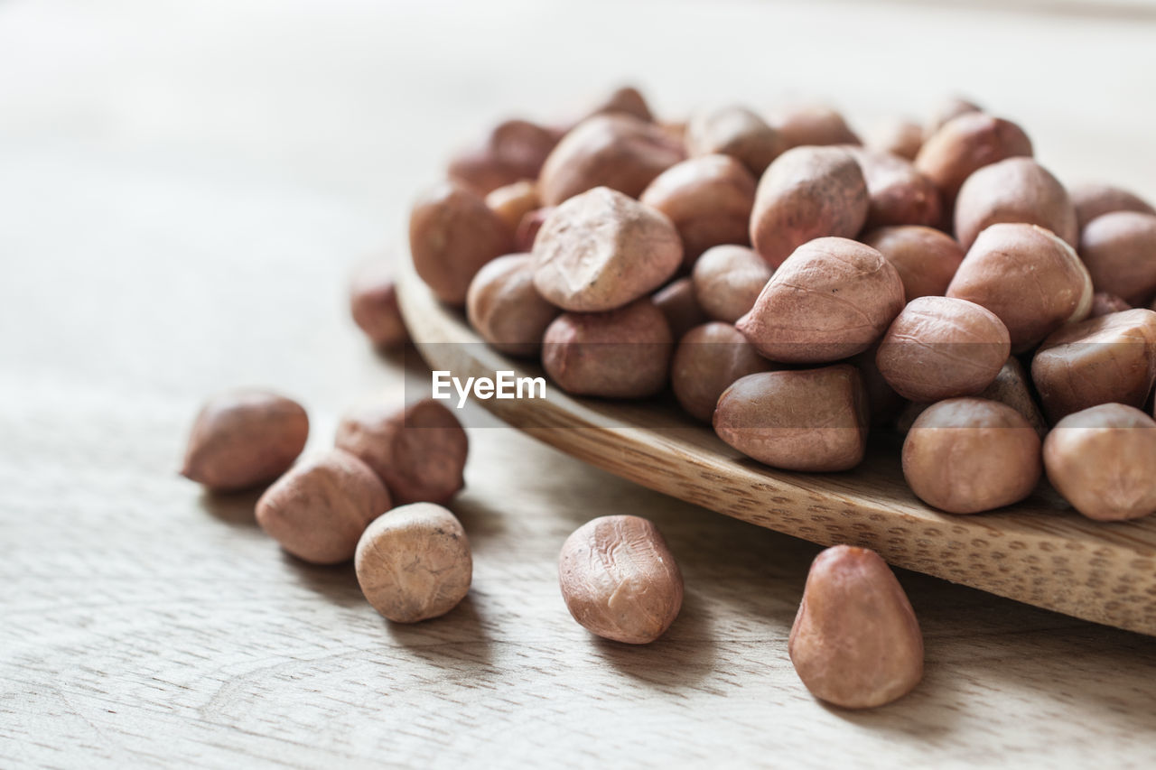 Close-up of hazelnuts with spoon on wooden table