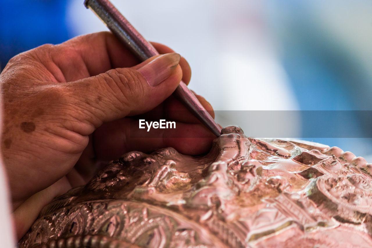 Cropped Hand Of Artist Carving Metal In Workshop