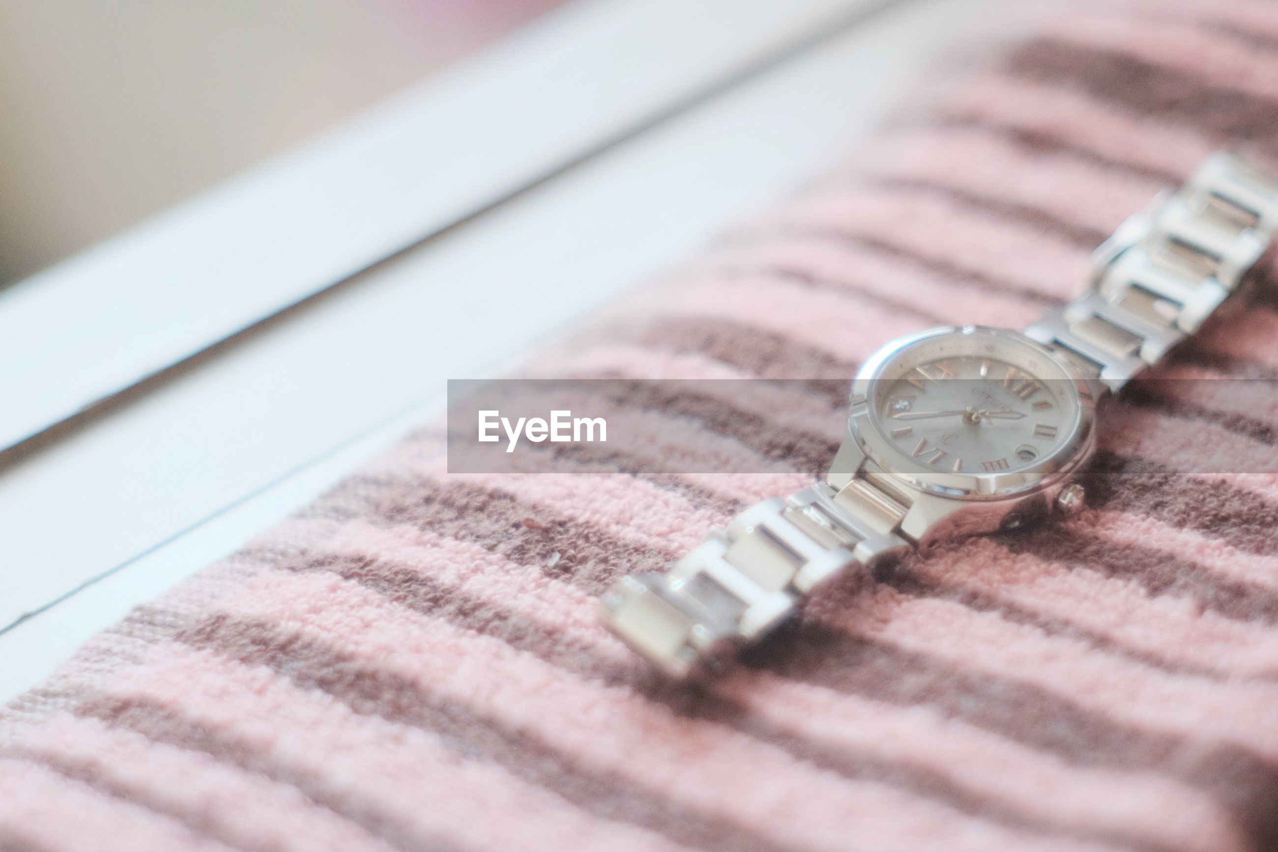 Close-up of wristwatch on bed at home