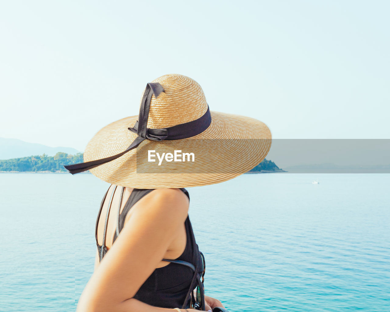 hat, water, real people, clothing, sea, one person, leisure activity, lifestyles, rear view, sun hat, sky, day, beauty in nature, women, nature, straw hat, scenics - nature, adult, clear sky, outdoors