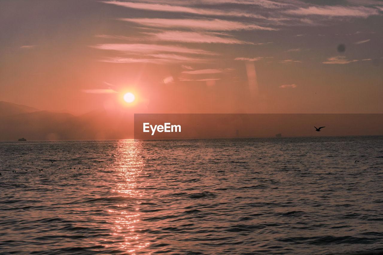 VIEW OF SEA AGAINST ORANGE SKY