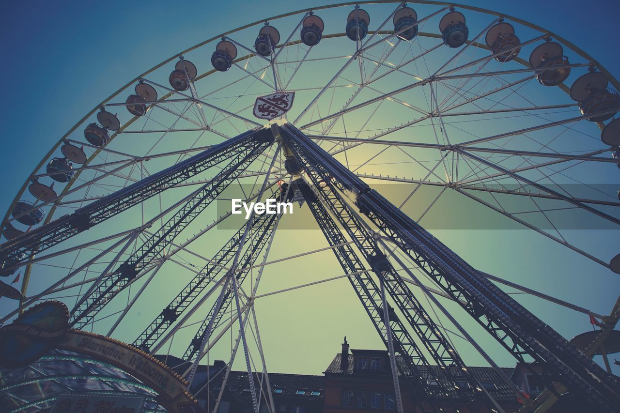 amusement park ride, amusement park, sky, low angle view, arts culture and entertainment, built structure, architecture, ferris wheel, nature, day, clear sky, no people, outdoors, building exterior, tall - high, leisure activity, fairground, large, travel destinations, circle, wheel
