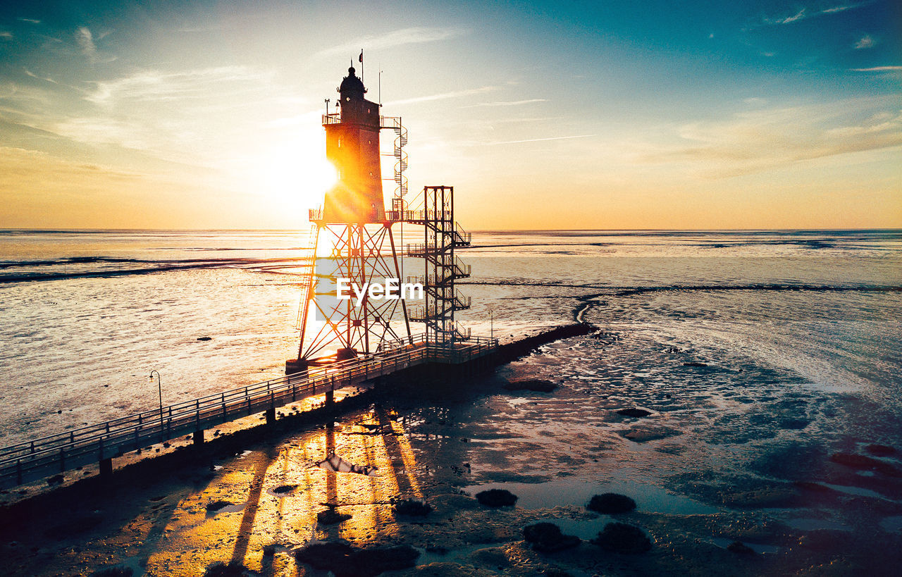 sea, sunset, water, horizon over water, sky, lighthouse, beauty in nature, nature, scenics, cloud - sky, tranquil scene, safety, tranquility, sunlight, sun, reflection, guidance, built structure, outdoors, architecture, no people, building exterior, beach, day
